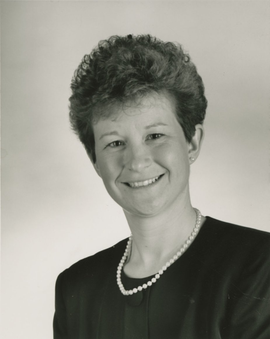 Image Description. Black and white photograph of a Caucasian woman with short brown hair, smiling.