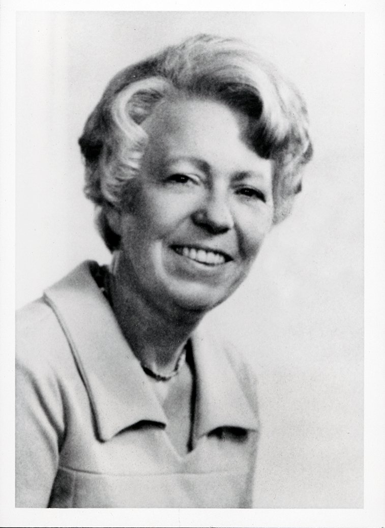 Image Description. Black and white photograph of a Caucasian woman with short, curled gray hair, smiling.