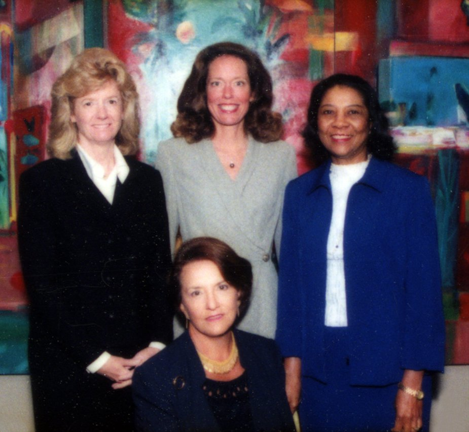 Image Description. Photograph of three women standing, two who are Caucasian and one woman of color. A Caucasian woman sits posed in front of the other three.