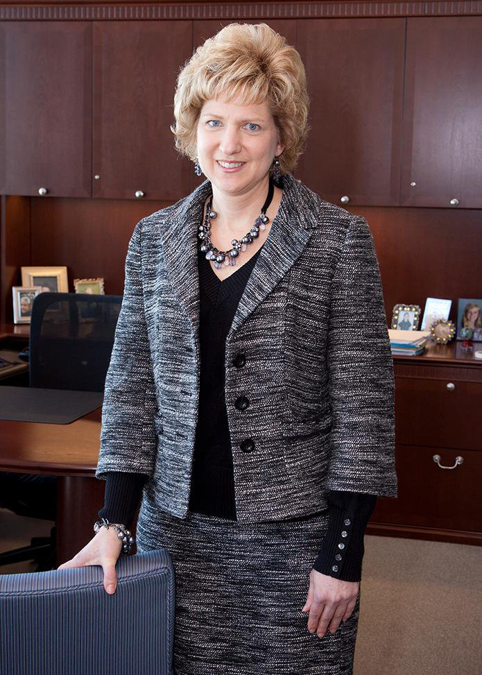 Image Description. Photograph of a Caucasian woman with short blond hair standing in an office, smiling.