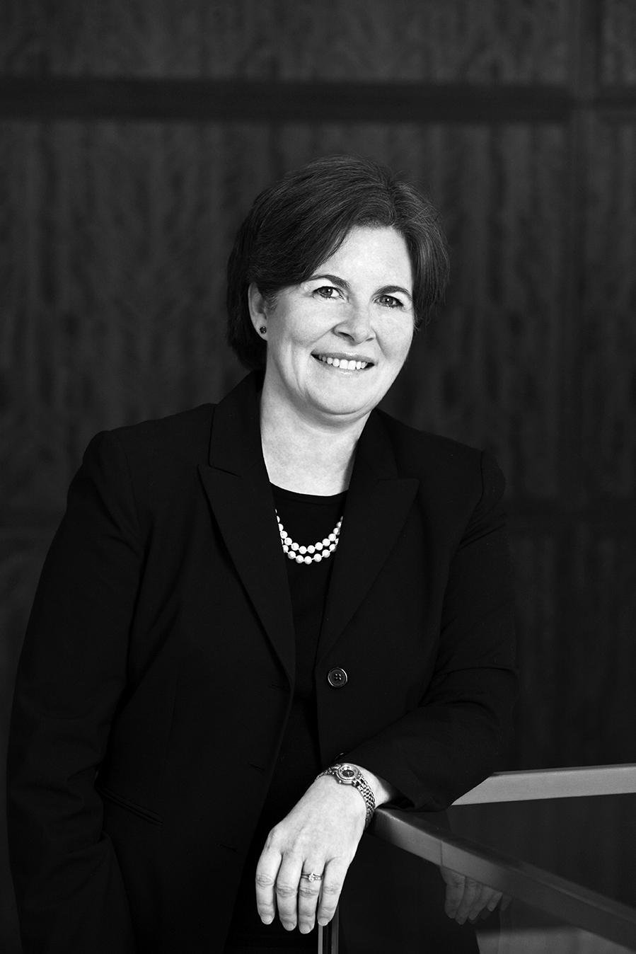 Image Description. Black and white photograph of a Caucasian woman with short brown hair standing in an office, smiling.