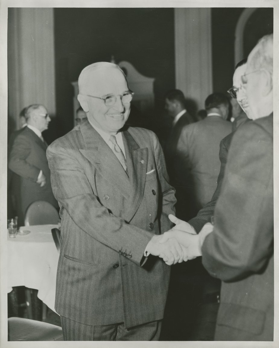 Image Description. Black and white photograph of President Truman smiling, shaking the hand of an unknown man in a large room with other men standing around tables.